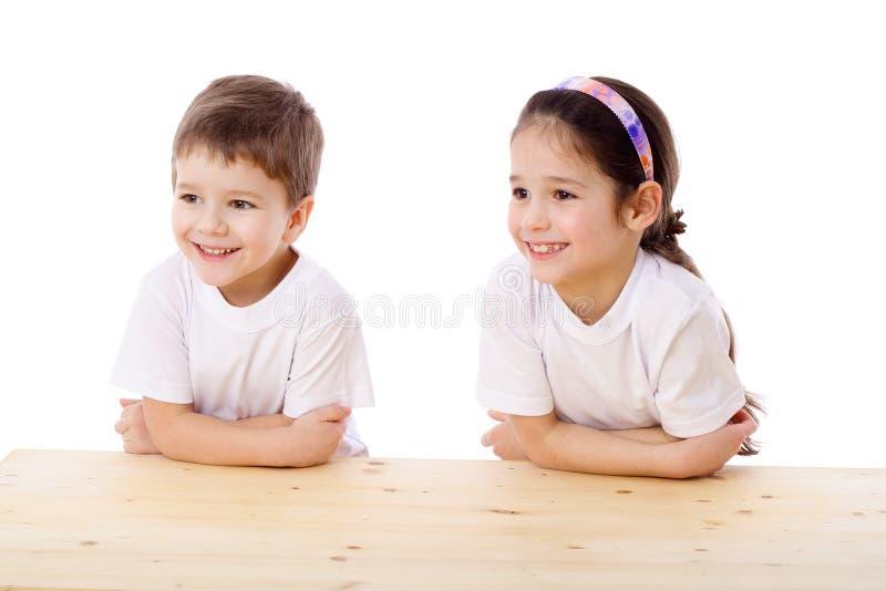 Due bambini sorridenti allo scrittorio fotografia stock libera da diritti