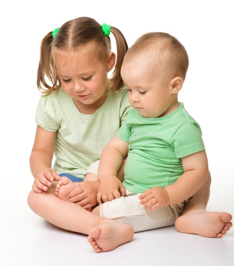 Due bambini stanno giocando sul pavimento fotografia stock