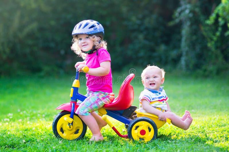 Due bambini su una bici nel giardino fotografia stock libera da diritti