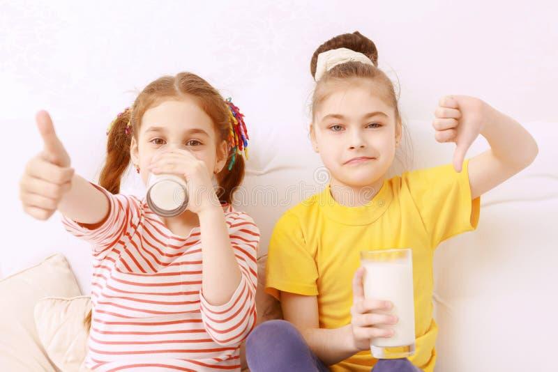 Due bambini svegli che giudicano latte fotografia stock