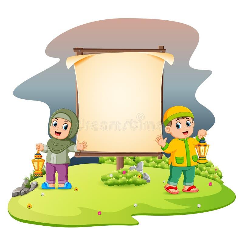 due bambini svegli con la lanterna del Ramadan sta stando vicino all'insegna in bianco nel giardino royalty illustrazione gratis