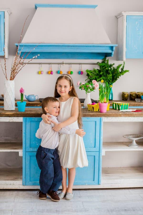 Due bambini svegli con le uova di Pasqua divertendosi nella cucina immagine stock
