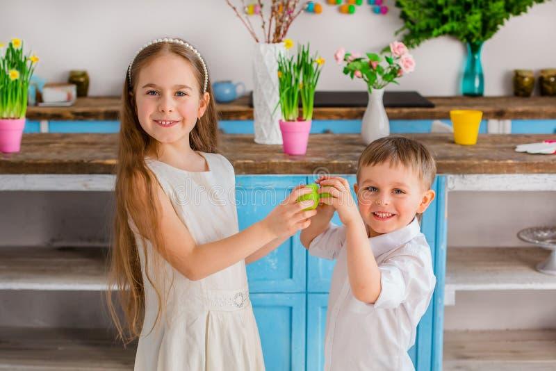 Due bambini svegli con le uova di Pasqua divertendosi nella cucina fotografia stock libera da diritti
