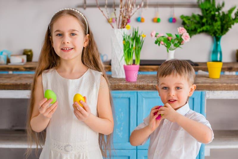 Due bambini svegli con le uova di Pasqua divertendosi nella cucina immagini stock libere da diritti