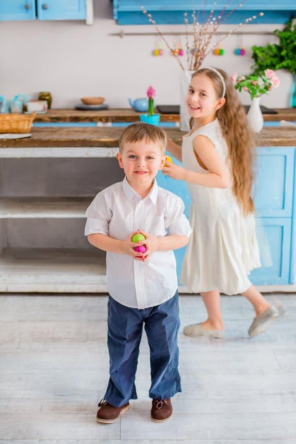 Due bambini svegli con le uova di Pasqua divertendosi nella cucina immagini stock