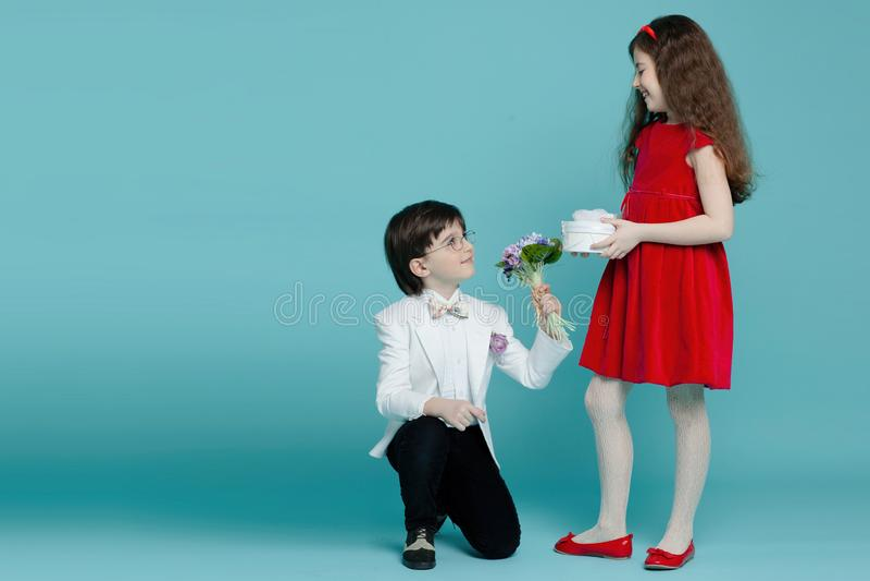 Due bambini in vestiti eleganti posa delicato, tenendo i fiori per lei, posanti nello studio, isolato su un fondo blu immagini stock libere da diritti