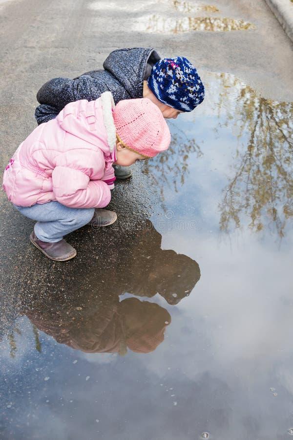 Due bambini vicino ad una pozza fotografia stock libera da diritti