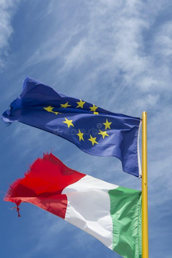 Due bandiere dell'Italia e dell'Unione Europea che fluttuano nel vento fotografia stock