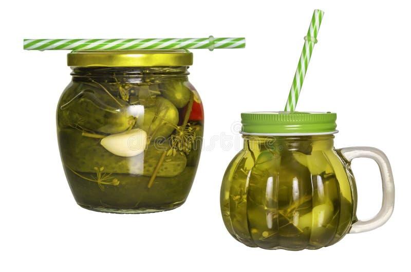 Due barattoli di vetro con i coperchi ed il tubo con il sottaceto del cetriolo isolato fotografie stock