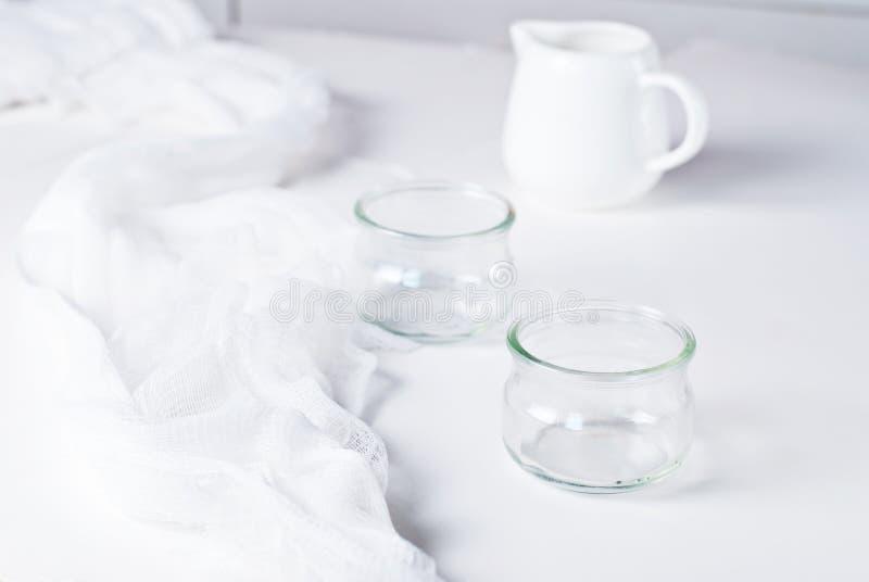 Due barattoli vuoti con la brocca di latte immagini stock