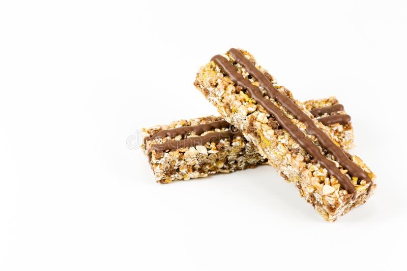 Due barre di granola con le strisce del cioccolato su fondo bianco fotografie stock