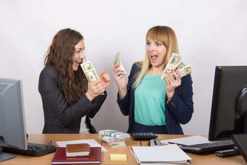 Due batuffoli felici della tenuta della segretaria felice di soldi in loro mani fotografia stock