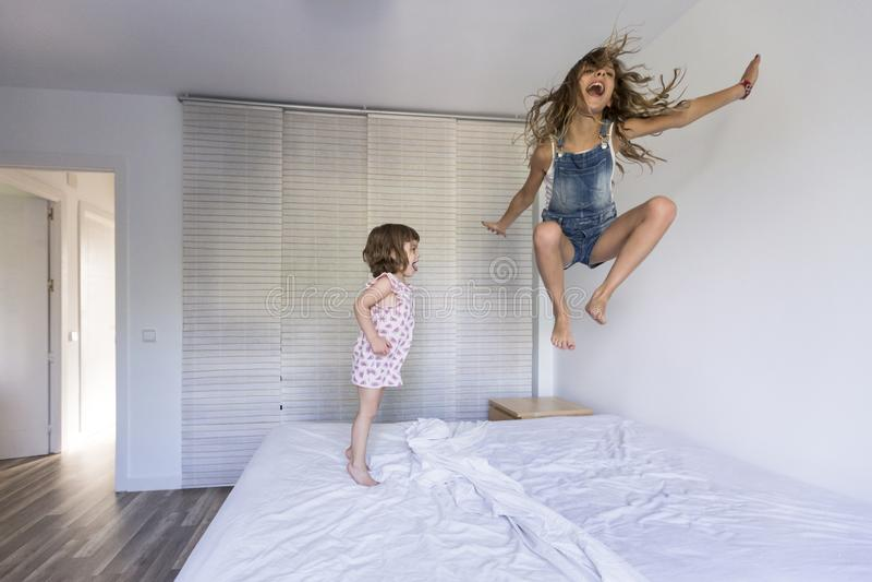Due bei bambini della sorella che giocano e che saltano sul letto a casa Divertimento all'interno Amore e stile di vita della fam fotografia stock libera da diritti