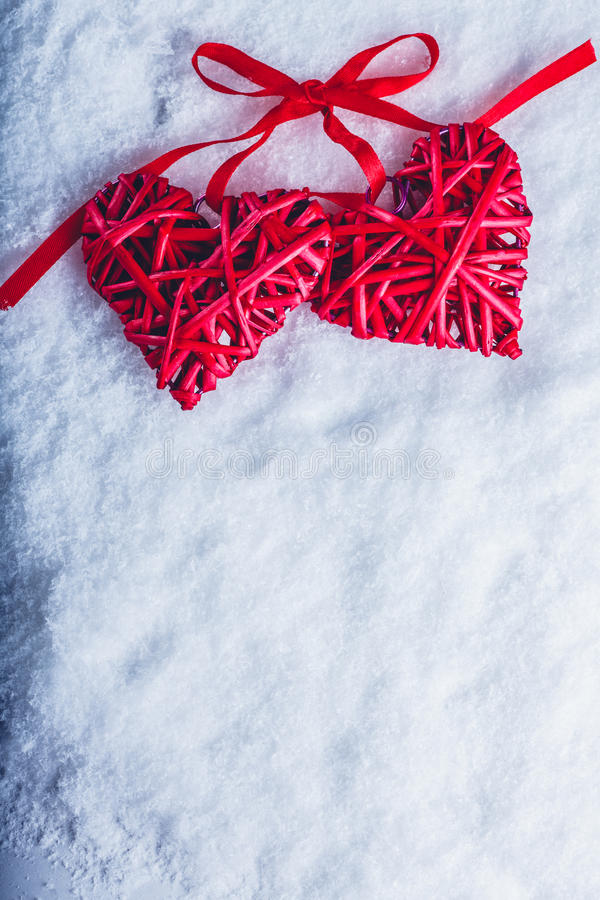 Due bei cuori rossi d'annata legati insieme ad un nastro su un fondo bianco della neve Amore e concetto di giorno di biglietti di fotografie stock