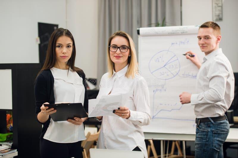 Due bei impiegati di concetto che hanno conversazione mentre strategia aziendale del disegno del collega dell'uomo sul grafico di immagini stock