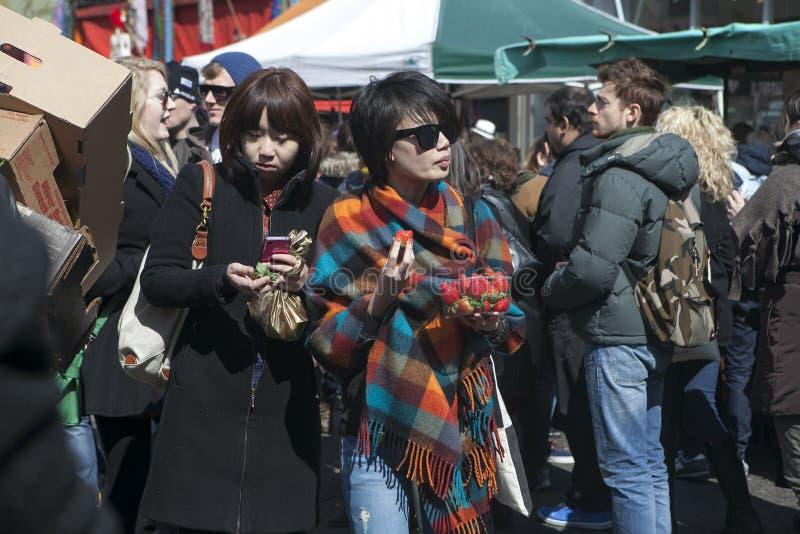 Due belle donne asiatiche con le fragole stanno facendo il loro modo attraverso la folla nel mercato immagini stock
