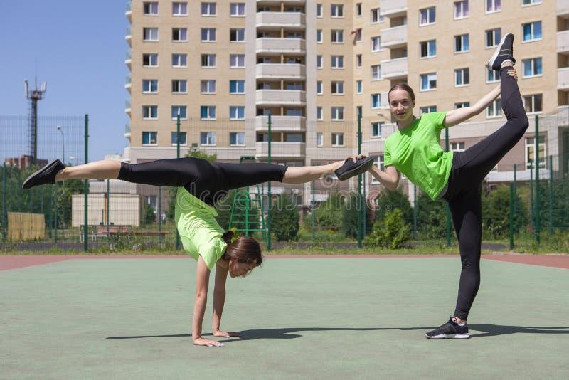 Due belle donne che allungano nel parco della città dopo l'attività di sport e correre immagine stock libera da diritti