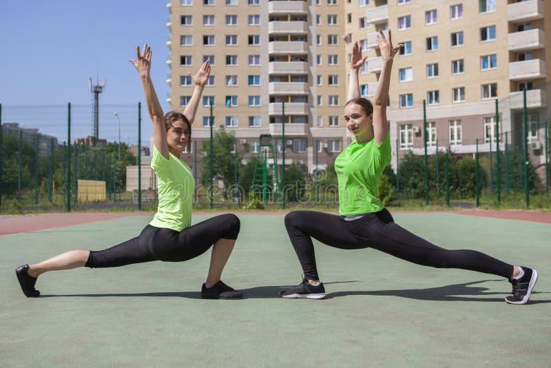 Due belle donne che allungano nel parco della città dopo l'attività di sport e correre fotografia stock