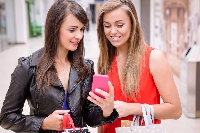 Due belle donne che esaminano telefono nel centro commerciale immagini stock libere da diritti