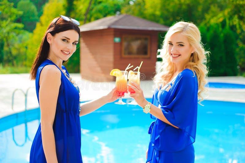 Due belle donne che hanno cocktail insieme dalla piscina fotografia stock libera da diritti