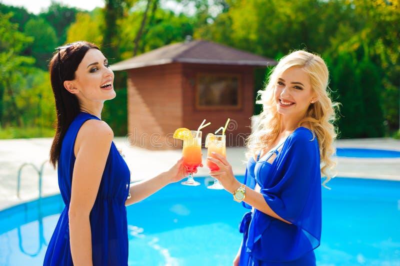 Due belle donne che hanno cocktail insieme dalla piscina immagini stock