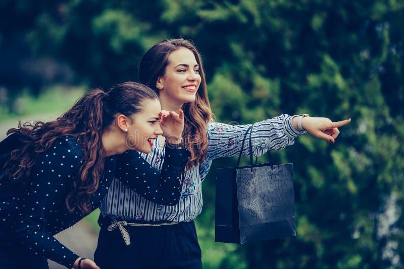 Due belle donne che hanno una conversazione di rilassamento mentre camminando nel parco dopo la compera immagine stock libera da diritti
