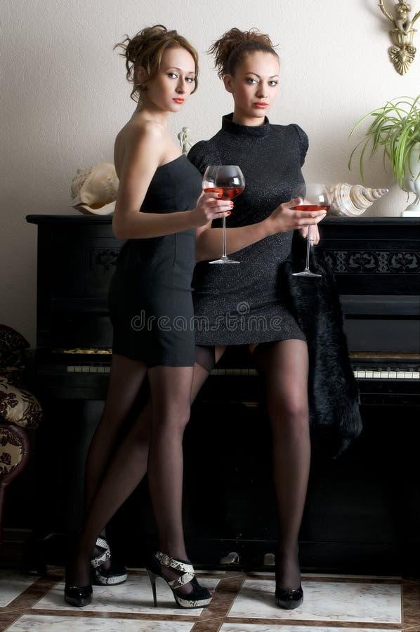 Due belle donne con vino rosso fotografia stock libera da diritti