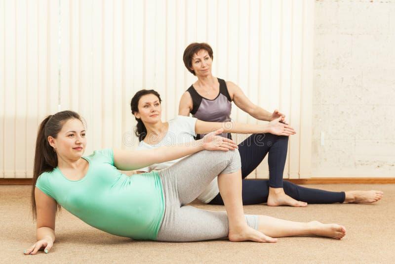 Due belle donne incinte che fanno yoga con un istruttore immagini stock libere da diritti
