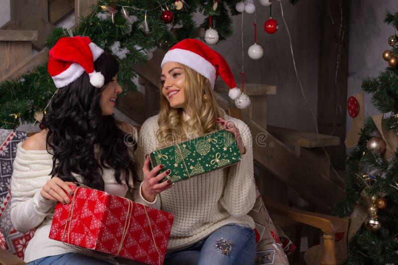 Due belle donne nei sorrisi dei cappelli di Santa scambiano i regali per Chri immagini stock libere da diritti