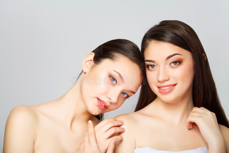 Due belle donne sexy che cosa che posa nello studio e che tiene crema fotografia stock libera da diritti