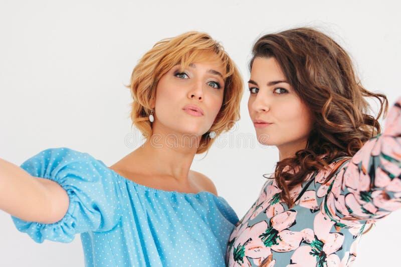 Due belle giovani donne affascinanti in vestito da estate che fa selfie sulla macchina fotografica frontale, isolata su fondo bia immagini stock