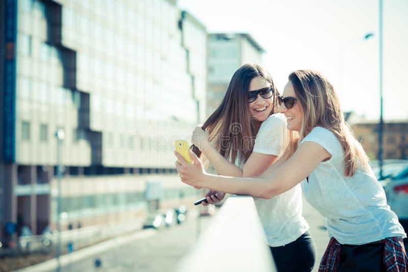 Due belle giovani donne che per mezzo dello Smart Phone fotografia stock libera da diritti