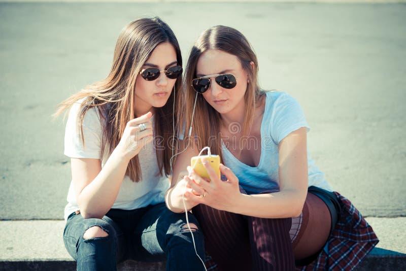 Due belle giovani donne che per mezzo dello Smart Phone immagine stock libera da diritti