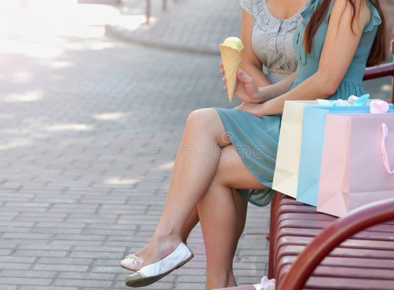 Due belle giovani donne che si siedono sul banco dopo la compera ed il cibo del gelato fotografie stock libere da diritti