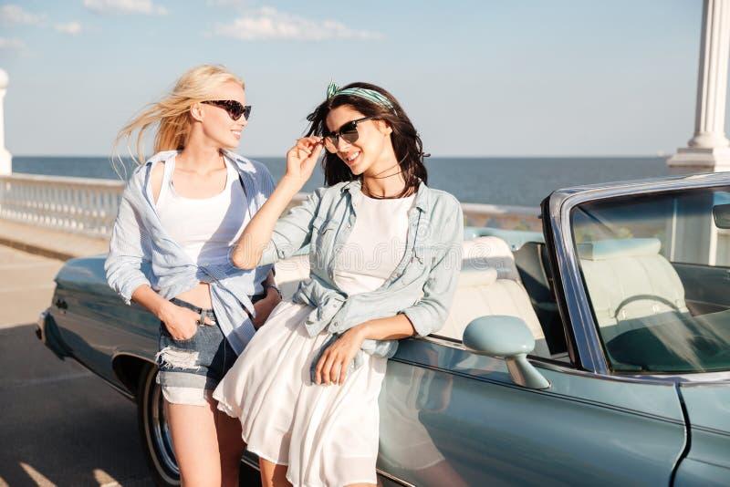 Due belle giovani donne che stanno cabriolet vicino fotografia stock