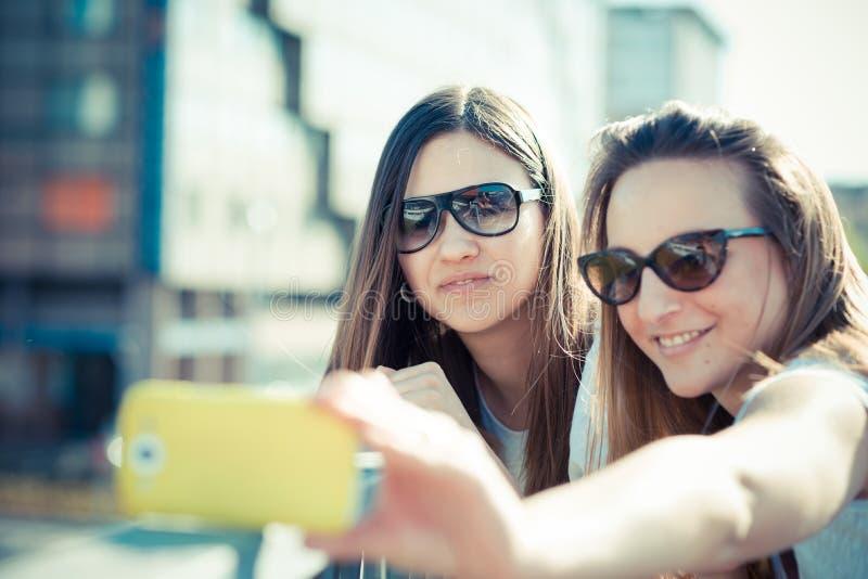 Due belle giovani donne che usando il selfie dello Smart Phone fotografia stock libera da diritti