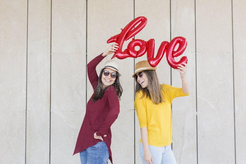 Due belle giovani donne divertendosi all'aperto con un pallone rosso con una forma di parola di amore Vestiti casuali Stanno port immagine stock libera da diritti
