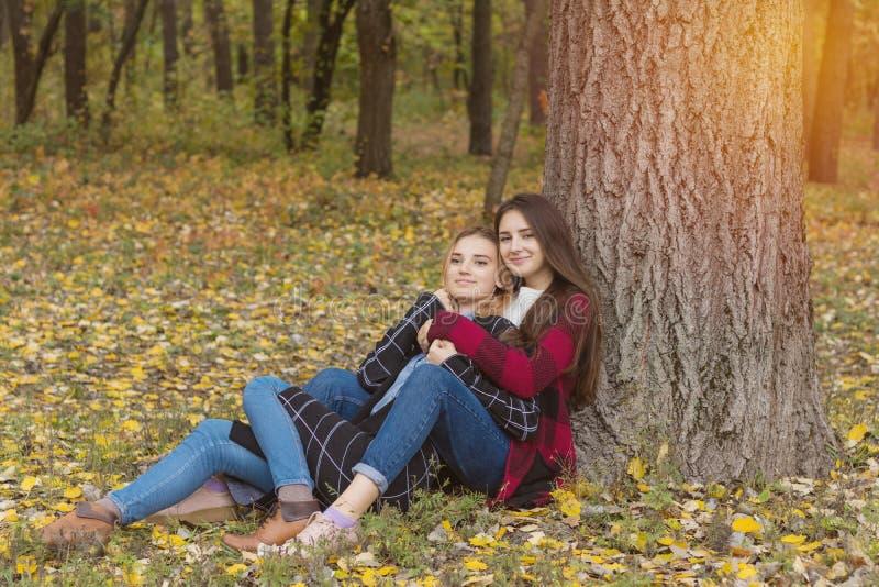 Due belle giovani donne sveglie che si rilassano nel parco immagini stock libere da diritti