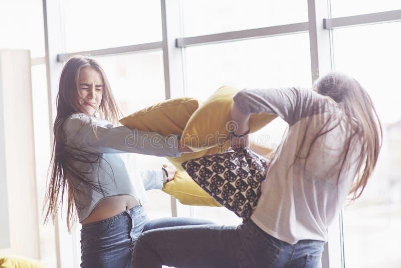 Due belle giovani sorelle dei gemelli che spendono insieme il tempo e stanno combattendo con i cuscini Fratelli germani divertend immagine stock