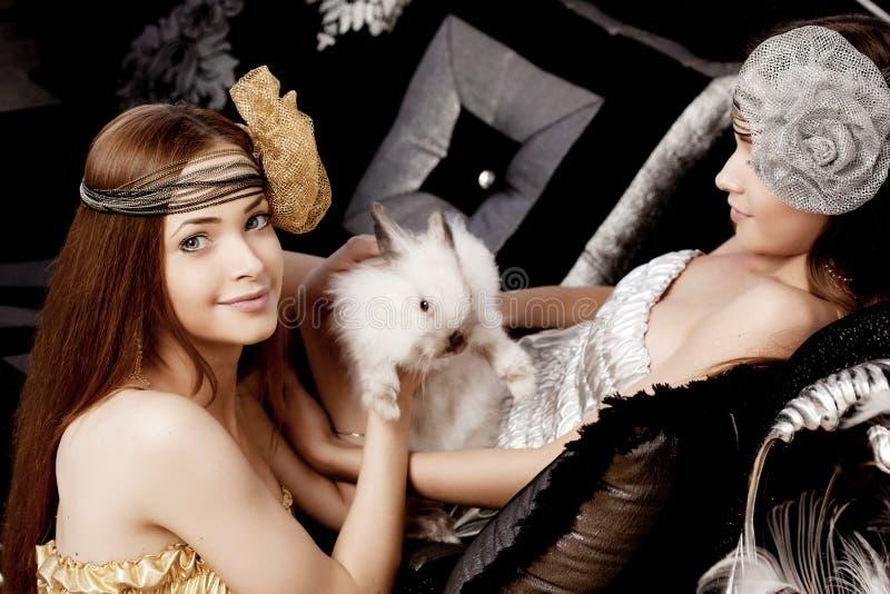 Due belle ragazze alla moda con un coniglio immagine stock libera da diritti