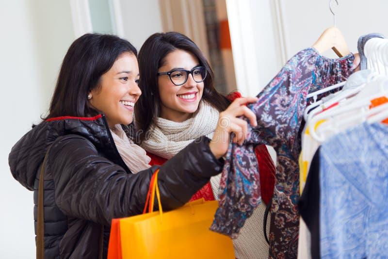 Due belle ragazze che comperano in un negozio di vestiti fotografia stock