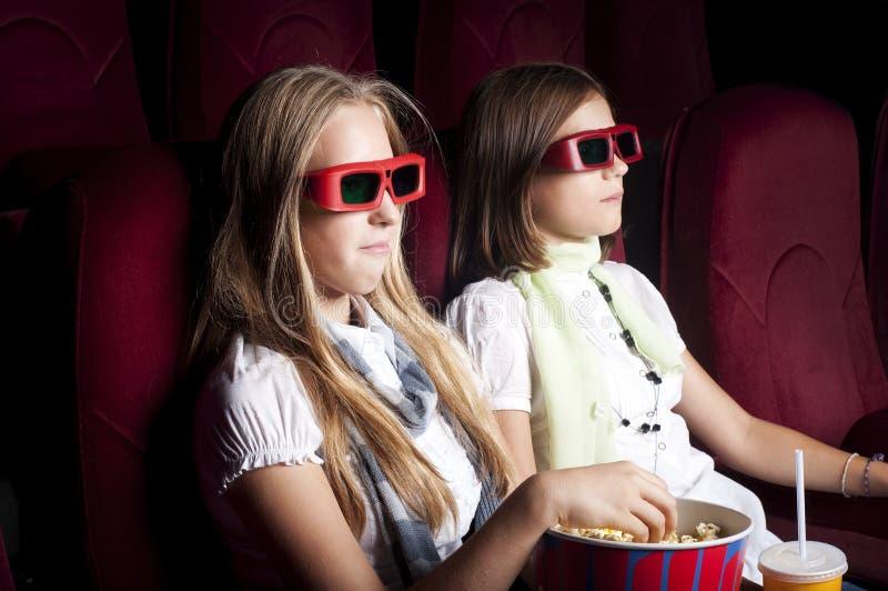 Due belle ragazze che guardano un film al cinematografo immagini stock