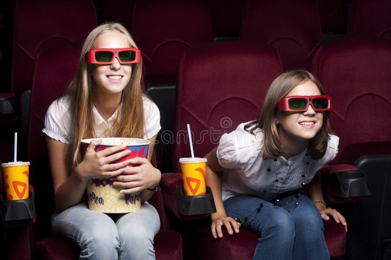 Due belle ragazze che guardano un film al cinematografo fotografia stock libera da diritti