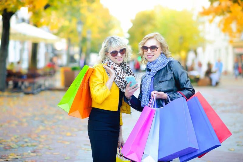 Due belle ragazze che stanno sulla via con i pacchetti di acquisto fanno un ordine dal telefono fotografia stock libera da diritti