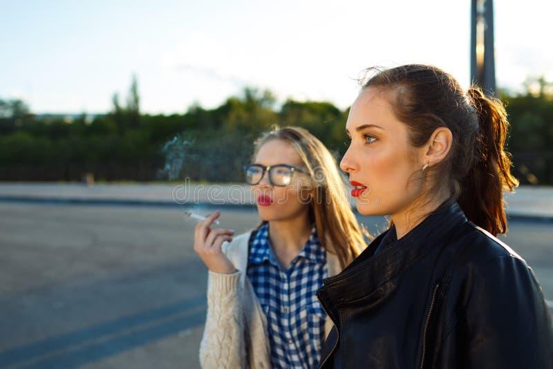 Due belle ragazze da fumare mentre aspettando all'aperto immagine stock