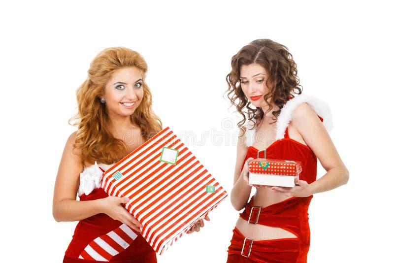 Due belle ragazze di natale hanno isolato i regali bianchi della tenuta del fondo immagine stock