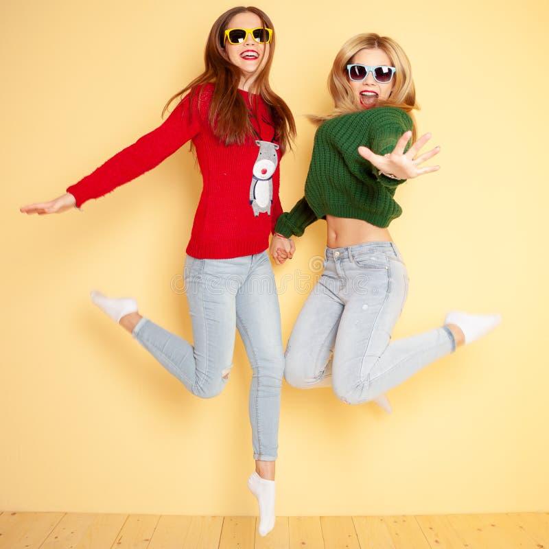 Due belle ragazze divertenti dei pantaloni a vita bassa in maglioni ed occhiali da sole Inverno e modo di concetto fotografie stock