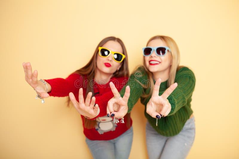 Due belle ragazze divertenti dei pantaloni a vita bassa in maglioni ed occhiali da sole Inverno e modo di concetto immagine stock