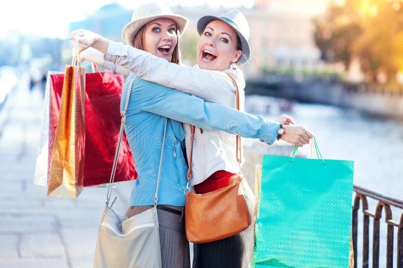 Due belle ragazze felici con l'abbraccio dei sacchetti della spesa nella città fotografia stock libera da diritti