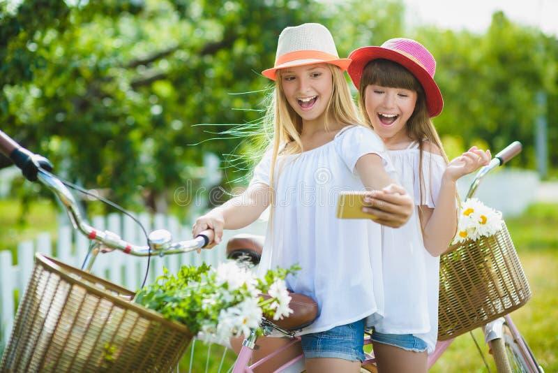Due belle ragazze felici dei pantaloni a vita bassa che ridono e che posano per la macchina fotografica con le bici immagini stock